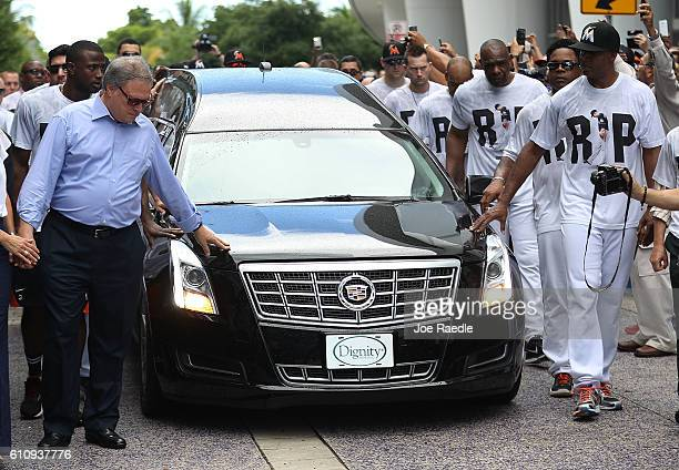 Miami Marlins owner Jeffrey Loria along with players and other members of the Marlins organization and their fans walk next to the hearse carrying...
