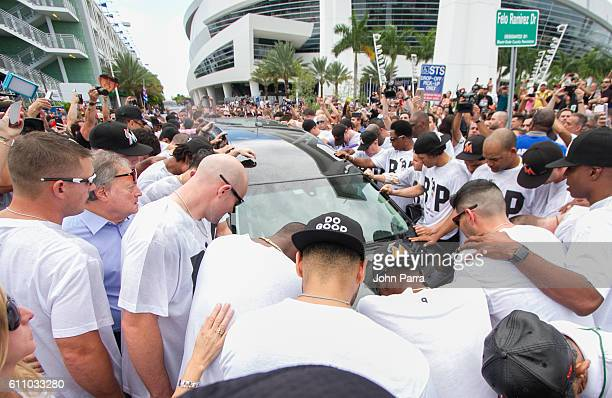 Miami Marlins owner Jeffrey Loria along with players and other members of the Marlins organization and their fans gather next to the hearse carrying...