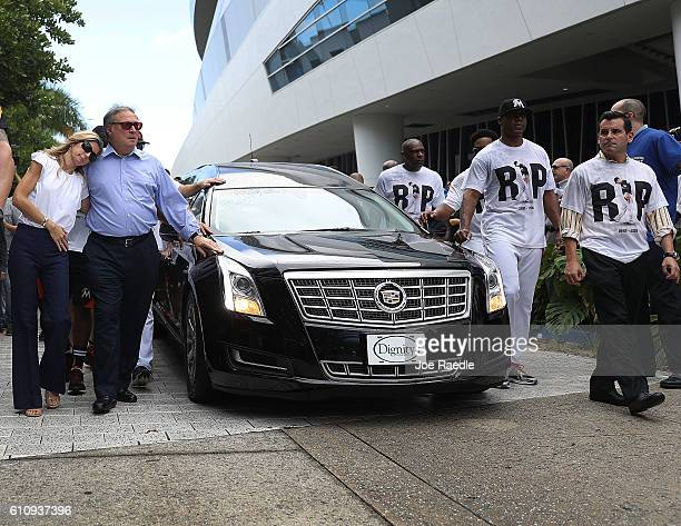 Miami Marlins owner Jeffrey Loria and his wife Julie Loria along with players and other members of the Marlins organization and their fans walk next...