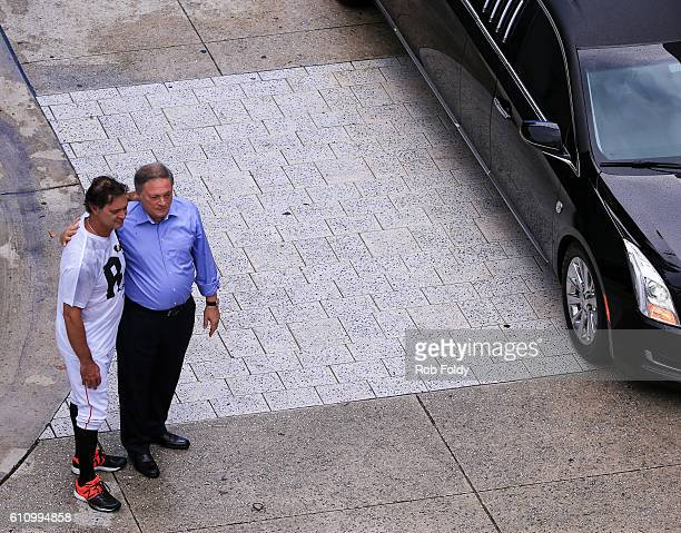Miami Marlins owner Jeffrey Loria right and manager Don Mattingly left look on as Miami Marlins players and members of the Marlins organization and...