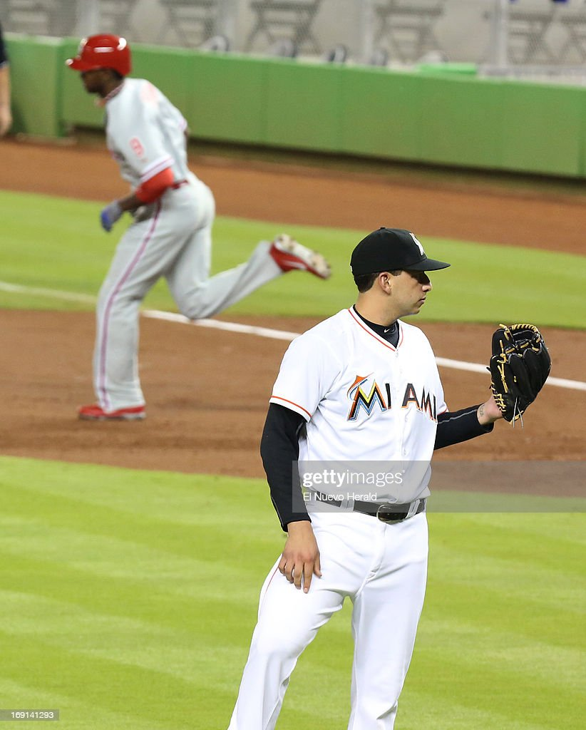 Miami Marlins pitcher Alex Sanabia waits for Philadelphia Phillies left fielder Domonic Brown to round the bases after a home run in the second inning at Marlins Park in Miami, Florida, Monday, May 20 2013.