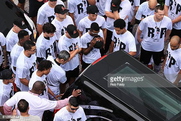 Miami Marlins players and members of the Marlins organization and their fans surround the hearse carrying Miami Marlins pitcher Jose Fernandez to pay...