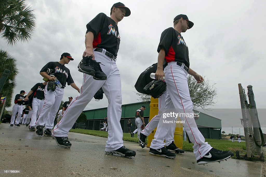 Miami Marlins players head to workouts in the rain out on the first day of full squad workouts at Marlins spring training camp at Roger Dean Stadium in Jupiter, Florida, Friday, February 15, 2013.