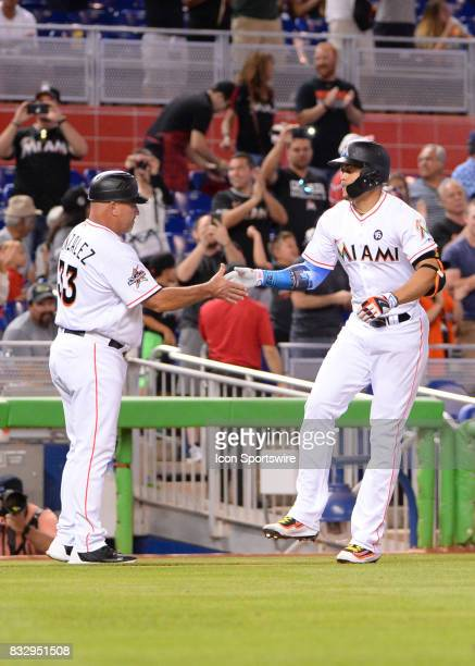 Miami Marlins right fielder Giancarlo Stanton hits home run number 43 turns on third base celebrates with Miami Marlins third base coach Fredi...