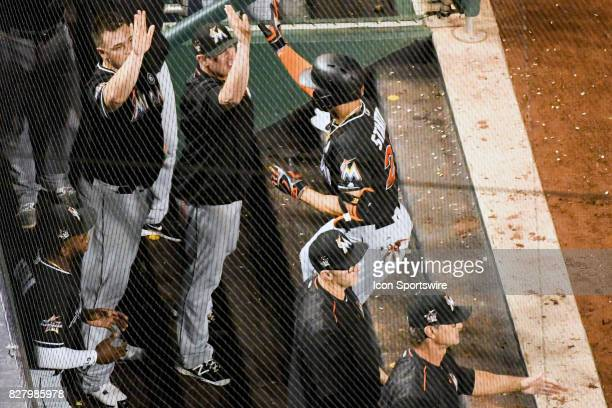 Miami Marlins right fielder Giancarlo Stanton is congratulated by ]starting pitcher Vance Worley in the dugout after hitting a fifth inning three run...
