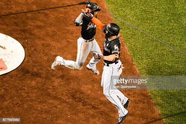 Miami Marlins right fielder Giancarlo Stanton is congratulated by Miami Marlins second baseman Dee Gordon after hitting a fifth inning three run home...