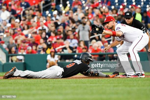 Miami Marlins second baseman Dee Gordon dives back into first base as Washington Nationals first baseman Ryan Zimmerman takes the throw in the third...