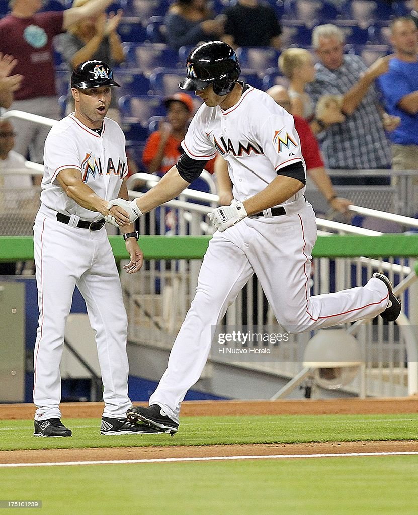 Miami Marlins third base coach Joe Espada greets Jake Marisnick after Marisnick hit a solo home run in the second inning against the New York Mets at Marlins Park in Miami, Florida, on Wednesday, July 31, 2013.