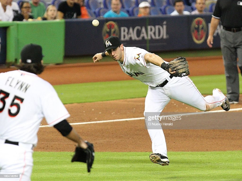 Miami Marlins third baseman Ed Lucas wobbles the ball while trying to throw to first base to get out Atlanta Braves left fielder Elliot Johnson in the fourth inning at Marlins Park in Miami, Florida, Thursday, September 12, 2013.