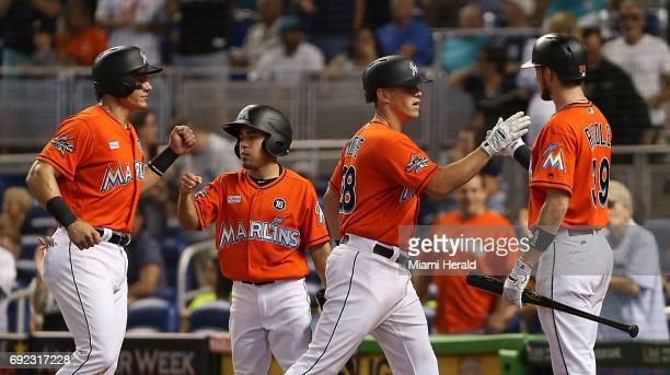 Miami Marlins' Tyler Moore is greeted by teammate JT Riddle right after his second inning threerun home run against the Arizona Diamondbacks on...