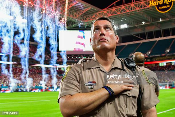 A Miami policeman puts his hand on his heart as the Star Spangled Banner American national anthem is played beforethe International Champions Cup...