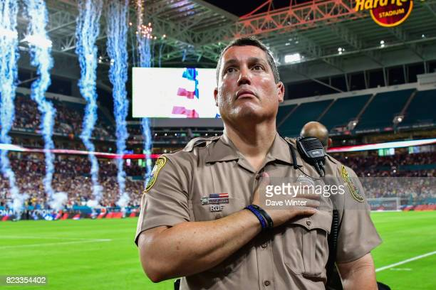 A Miami policeman puts his hand on his heart as the Star Spangled Banner American national anthem is played before the International Champions Cup...