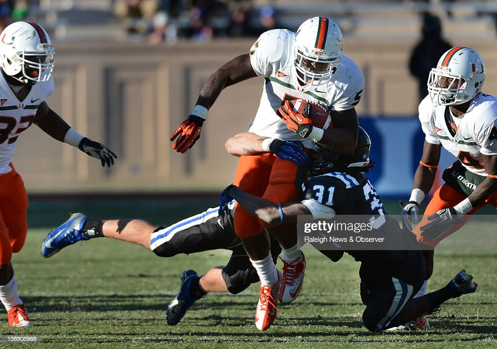 Miami running back Mike James (5) is stopped after a short gain by Duke cornerback Tony Foster (31) in the fourth quarter at Wallace Wade Stadium on Saturday, November 24, 2012, in Durham, North Carolina. The Miami Hurricanes defeated the Duke Blue Devils, 52-45.