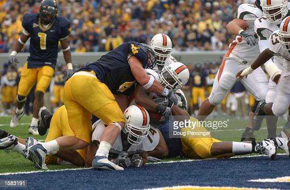 Miami running back Willis McGahee powers into the endzone to make a second quarter touchdown as WVU defender Grant Wiley tries to make the stop...