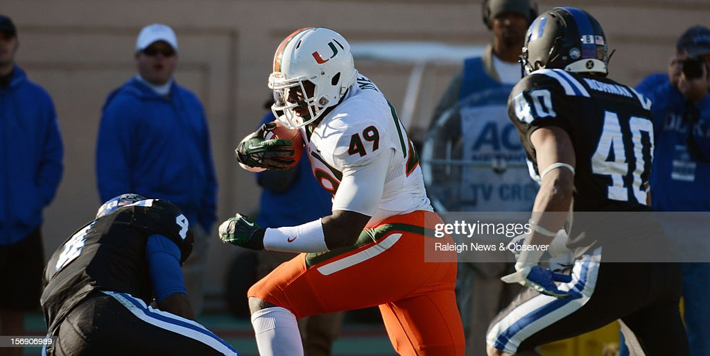 Miami tight end Dyron Dye (49) attempts to avoid Duke safety Walt Canty (4) as safety Dwayne Norman (40) closes in during a third quarter play at Wallace Wade Stadium on Saturday, November 24, 2012, in Durham, North Carolina. The Miami Hurricanes defeated the Duke Blue Devils, 52-45.