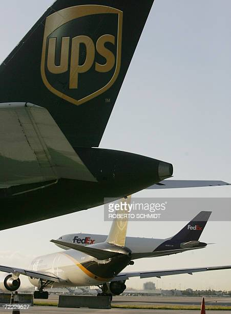 A United Parcel Service cargo plane sits on the tarmac and another one taxis into the runway as a cargo plane from Federal Express lands at Miami's...