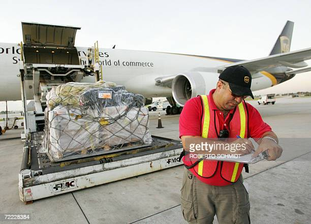 A United Parcel Service supervisor keeps track of packages being loaded into a cargo plane at the company's air hub for Latin America in Miami...