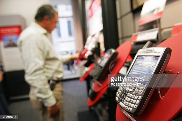 Oswaldo Betancourt looks at some of the latest mobile phones at a Verizon store in downtown Miami 02 November 2006 Verizon is a US broadband and...
