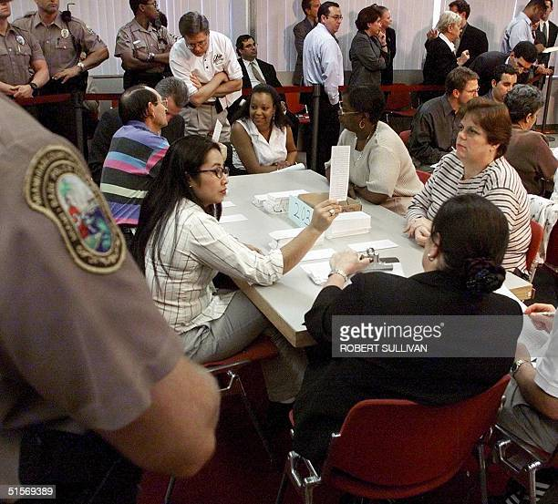 MiamiDade County election officials and representatives of the Republican and Democratic parties hand recount presidential ballots 14 November 2000...
