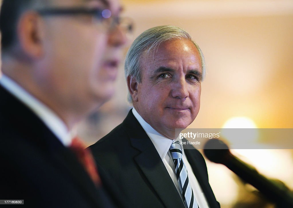 Miami-Dade County Mayor Carlos A. Gimenez, listens as Miami International Airport Aviation Director Emilio T. González, speaks to the media regarding the U.S. Justice Department and state attorneys general suit against the American Airlines and US Airways merger on August 21, 2013 in Miami, Florida. The Mayor and aviation director addressed the letter they sent Attorney General Eric H. Holder, Jr. in which they stated their concerns with the review of the merger due to the damage it will do to the local economy if the merger isn't allowed to go through.