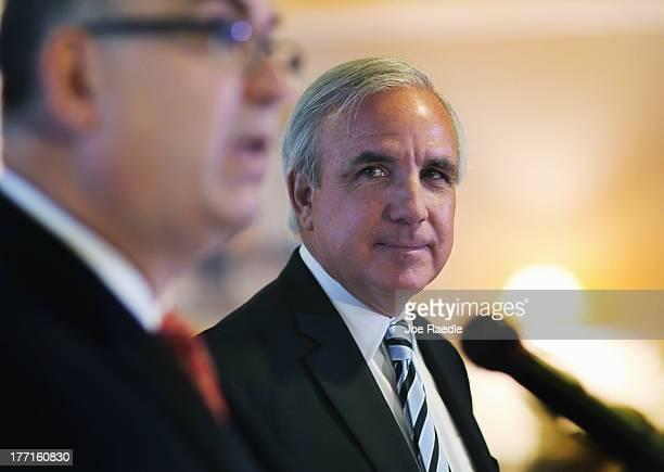 MiamiDade County Mayor Carlos A Gimenez listens as Miami International Airport Aviation Director Emilio T González speaks to the media regarding the...