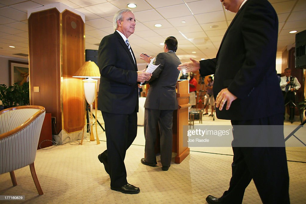Miami-Dade County Mayor Carlos A. Gimenez, (L) prepares to shake hands with Miami International Airport Aviation Director Emilio T. González, after they spoke to the media regarding the U.S. Justice Department and state attorneys general suit against the American Airlines and US Airways merger on August 21, 2013 in Miami, Florida. The Mayor and aviation director addressed the letter they sent Attorney General Eric H. Holder, Jr. in which they stated their concerns with the review of the merger due to the damage it will do to the local economy if the merger isn't allowed to go through.