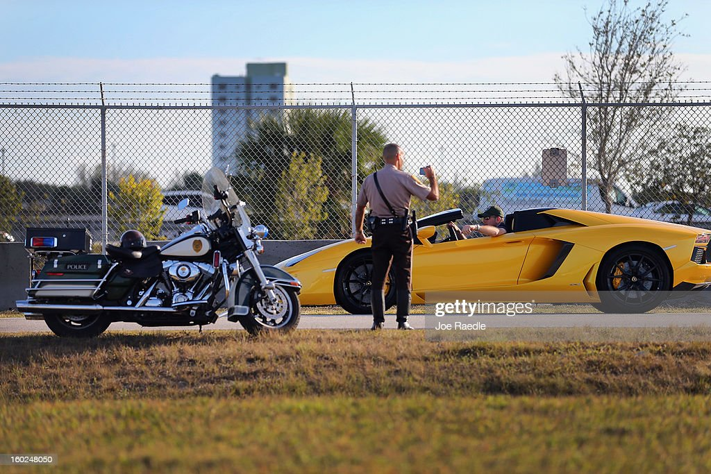A Miami-Dade police officer takes pictures of a new Lamborghini Aventador LP700-4 Roadster as it is seen at the Miami International Airporton January 28, 2013 in Miami, Florida. The world wide unveiling of the new luxury super sports cars took place at the airport.