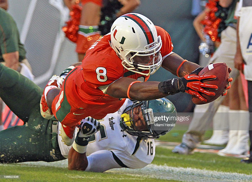 Miami's Duke Johnson dives for a third-quarter touchdown as South Florida's Reshard Cliett tries to make the stop at Sun Life Stadium in Miami Gardens, Florida, on Saturday, November 17, 2012. Miami rolled, 40-9.