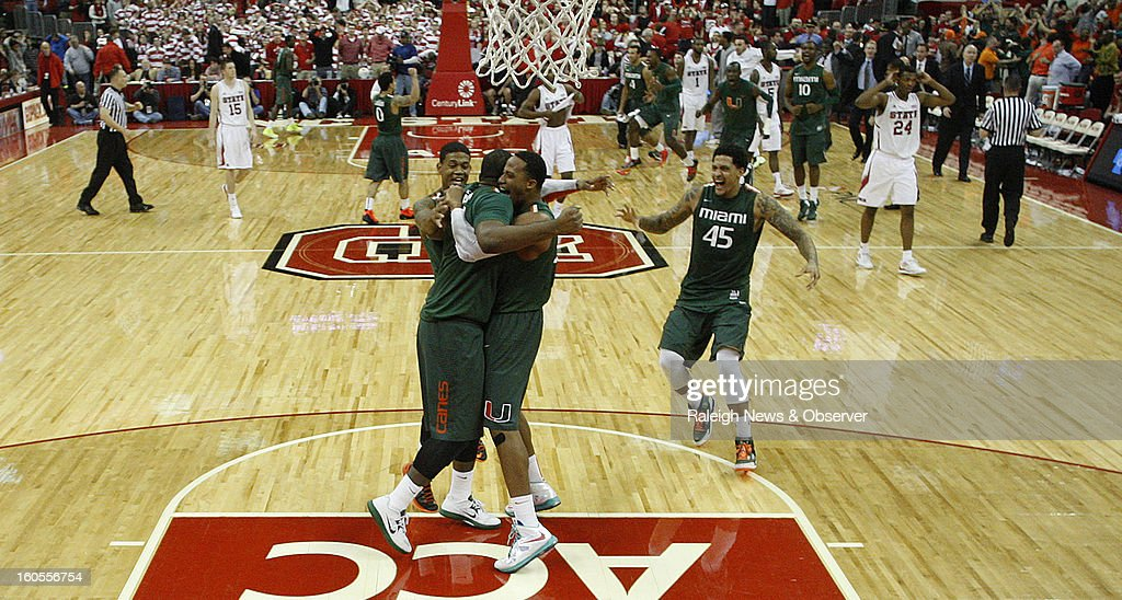 Miami's Reggie Johnson (42), center left, and Kenny Kadji (35), hug as Miami's Rion Brown (15), left, and Julian Gamble (45), right, come in to celebrate after a 79-78 victory over North Carolina State at PNC Arena in Raleigh, North Carolina, on Saturday, February 2, 2013.