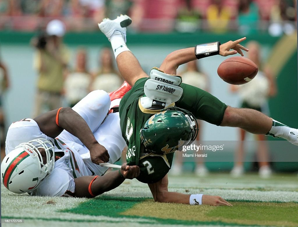 Miami's Shayon Green sacks South Florida quarterback Steven Bench, who funnels the ball in the endzone during the second quarter at Raymond James Stadium in Tampa, Florida, Saturday, September 28, 2013. Miami's Jimmy Gaines recovers the ball for a touchdown. Miami defeated USF, 49-21.