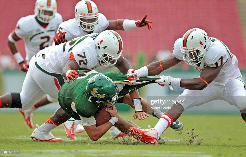 Miami's Tyriq McCord, (17) and Earl Moore, ( 72), sack South Florida quarterback Steven Bench in the fourth quarter at Raymond James Stadium in Tampa, Florida, Saturday, September 28, 2013. Miami defeated USF, 49-21.