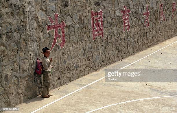 Miao minority boy standing against the wall of the playground of a village school Basha Guizhou Province China May 2004
