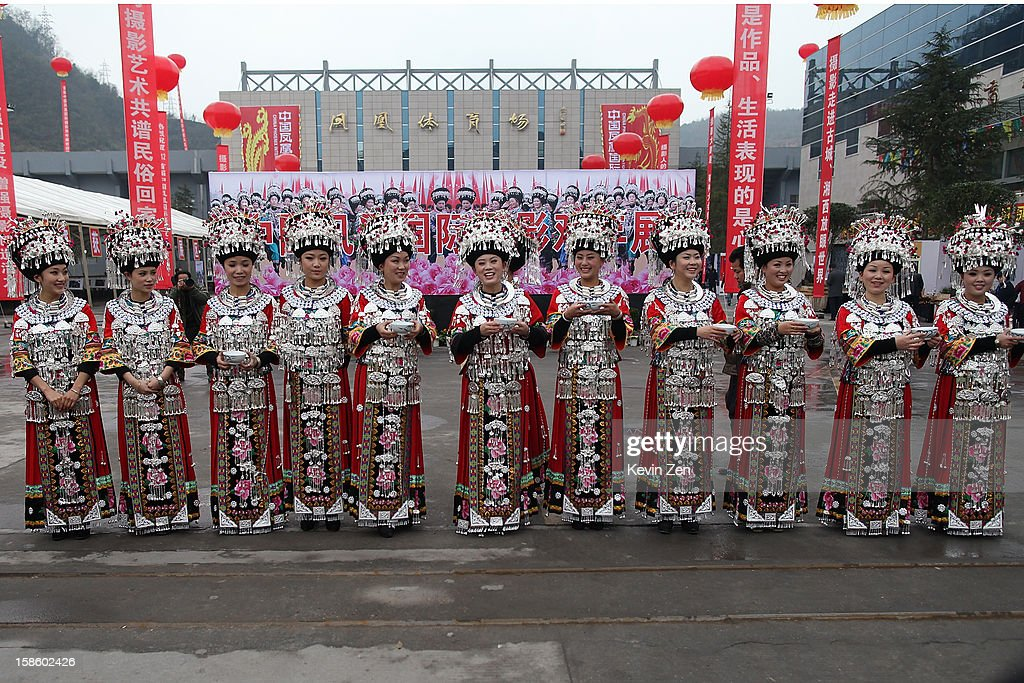 Miao women wear traditional clothing and jewelry at a stadium for a local event on December 18, 2012 in Fenghuang, China. Fenghuang Town was built by Emperor Kangxi in 1704 and after 300 years, the city's ancient appearance has been well preserved. Hunan is located in southwest Hunan Provience of China with a population of 370,000 within a total area of 1700 square kilometers.
