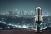 Wooden surface with microphone on blurry night city background with copy space. 3D Rendering