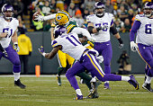Micah Hyde of the Green Bay Packers intercepts a pass intended for Mike Wallace of the Minnesota Vikings during the third quarter of their game at...