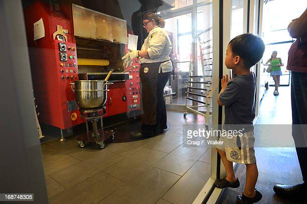 Micah Lin watches pastry chef Abby Fernandez make cakes in the Baumkuchen oven at Glaze the Baum Cake Shoppe in Denver CO May 14 2013 Entrepreneur...