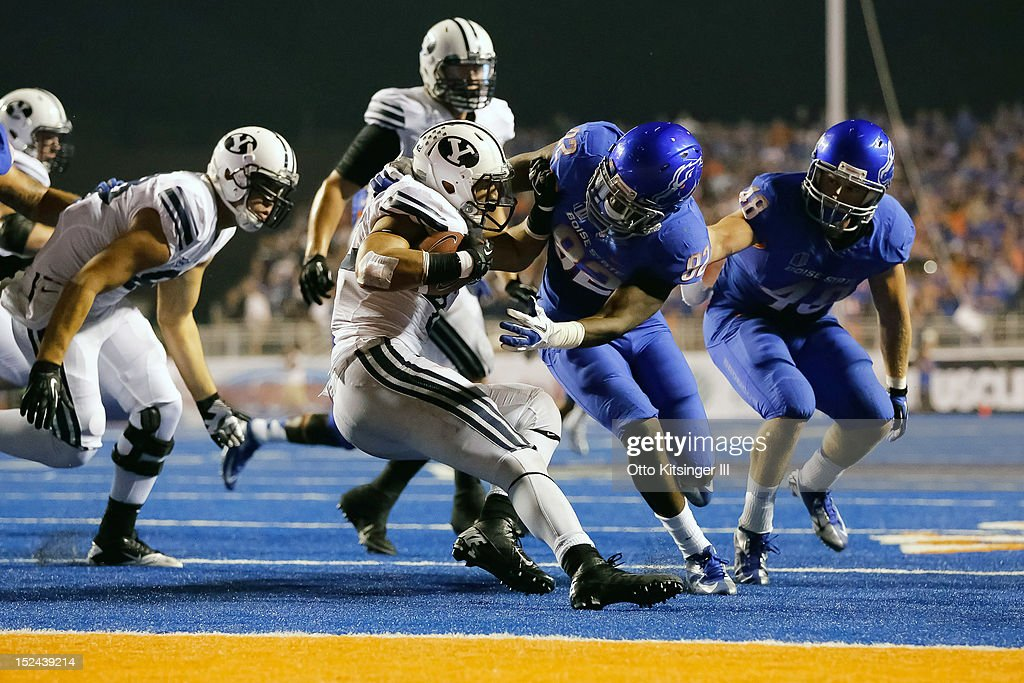 Michael Alisa #42 of the BYU Cougars tries to evade a tackle by Samuel Ukwuachu #82 of the Boise State Broncos at Bronco Stadium on September 20, 2012 in Boise, Idaho.