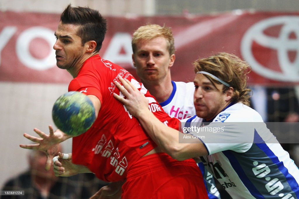 Michael Allendorf of Melsungen is challenged by Joakim Larsson and Marius Liebald (L-R) of Grosswallstadt during the Toyota Handball Bundesliga match between T VGrosswallstadt and MT Melsungen at f.a.n. frankenstolz arena on November 11, 2011 in Aschaffenburg, Germany.