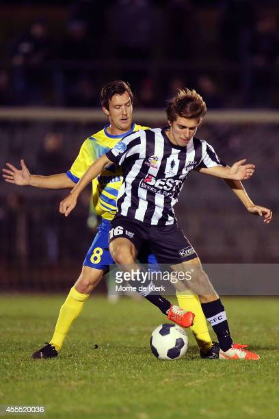Michael Angus of the Strikers competes for the ball with Thomas Love of Adelaide during the FFA Cup match between Adelaide City and the Brisbane...