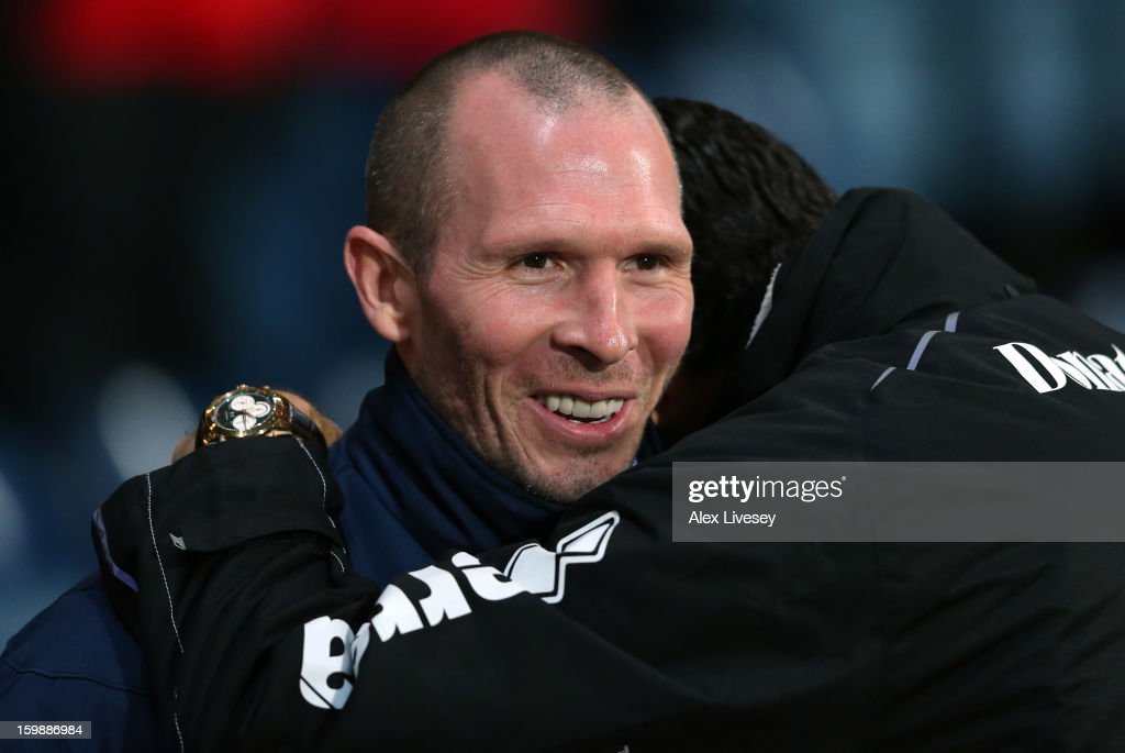 Michael Appleton the manager of Blackburn Rovers is hugged by Gus Poyet the manager Brighton & Hove Albion prior to the npower Championship match between Blackburn Rovers and Brighton & Hove Albion at Ewood park on January 22, 2013 in Blackburn, England.