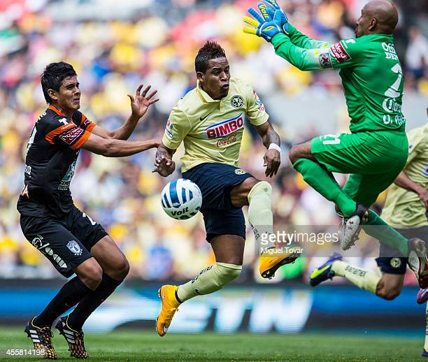 Michael Arroyo of America tries to shoot the ball on target as Oscar Perez and Miguel Herrera of Pachuca try to defend the goal during a match...