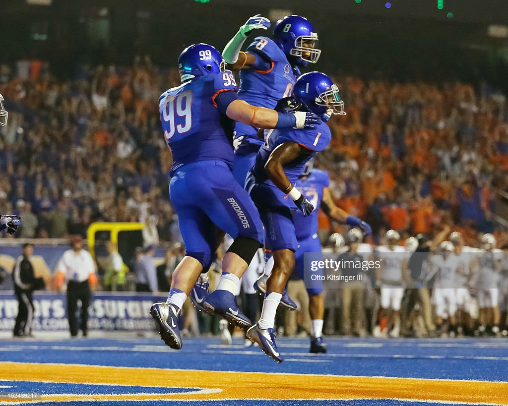 Michael Atkinson #99, Demarcus Lawrence #8, and Bryan Douglas #1 of the Boise State Broncos celebrate after a play against the BYU Cougars at Bronco Stadium on September 20, 2012 in Boise, Idaho.