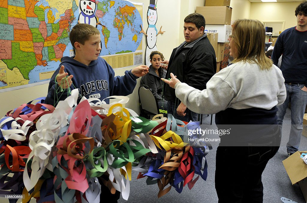 Michael Avery, 11, of Billerica, Massachusetts, left, delivers 26 handmade 3D snowflakes to the Connecticut Parent Teacher Student Association in Hamden, Connecticut, Friday, December 28, 2012. The PTSA is the collection center for the snowflake project to create a Winter Wonderland for the kids of Sandy Hook Elementary School. Beth Lubenow, a part-time worker a the office takes some of the snowflakes, so Michael can have his photo taken in front of the maps behind him, where push-pins are being placed from each state and country that sent items for the collection. Michael Baldarelli and Sabrina Fronte, center, worke on the maps, and Jake Blumenfeld, right, helped with sorting packages.