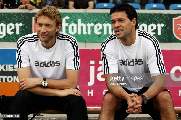 Michael Ballack chats with team mate Simon Rolfes before the preseason friendly match between SCR Altach and Bayer 04 Leverkusen on July 25 2010 in...