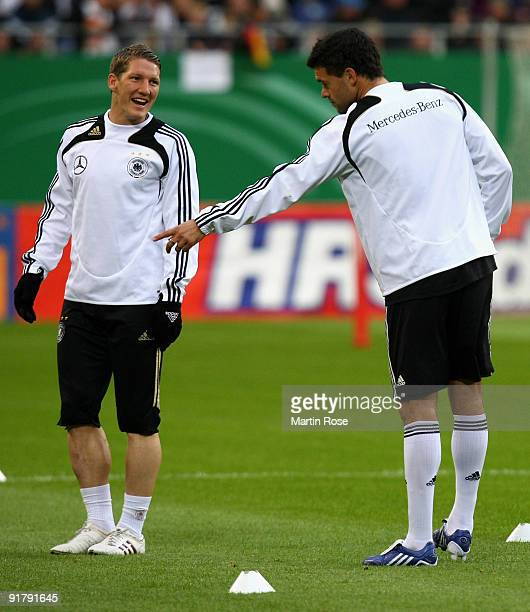 Michael Ballack jokes with Bastian Schweinsteiger during the German National Team training session at the Hamburg Arena on October 12 2009 in Hamburg...