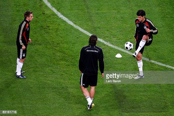 Michael Ballack kicks the ball next to Philipp Lahm and Mario Gomez during the training session of the German National team at the TUI Arena on...