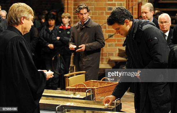 Michael Ballack lights a candle during a church service for German national goalkeeper Robert Enke at the 'Marktkirche' on November 11 2009 in...