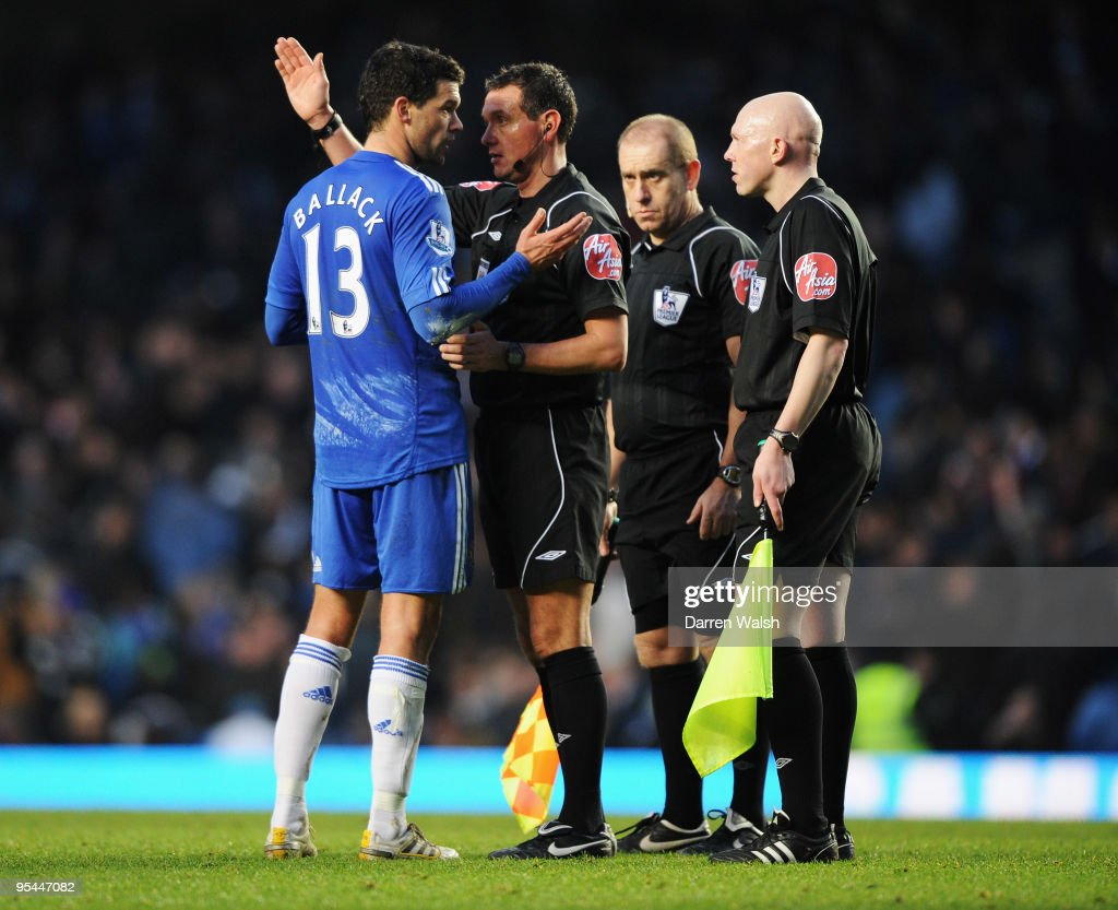 Michael Ballack of Chelsea talks to referee Andre Marriner and assistant referees Paddy Keane and Adam Watts during the Barclays Premier League match...
