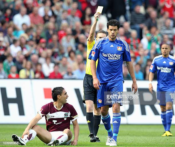 Michael Ballack of Leverkusen is booked by Referee Guido Winkmann during the Bundesliga match between Hannover 96 and Bayer Leverkusen at AWD Arena...