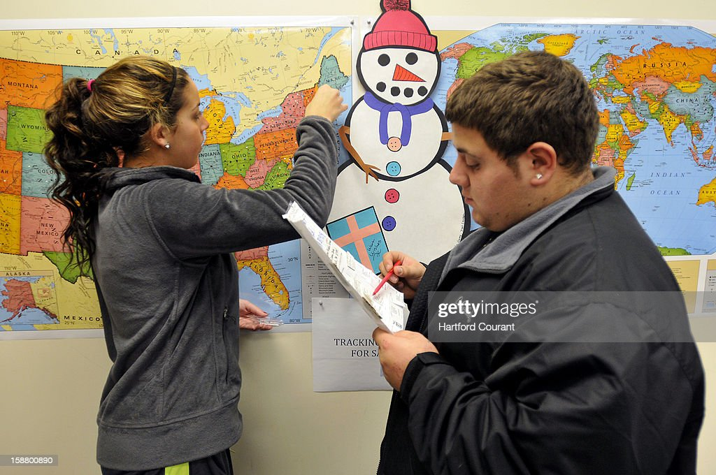 Michael Bardarelli reads off the state while Sabrina Fronte, 14, places a push-in in the maps of the country and world where a parcels for the Snowflakes Project came from at the Connecticut Parent Teacher Student Association, which is collecting the snowflakes to create a Winter Wonderland for the kids of Sandy Hook Elementary School, in Hamden, Connecticut, Friday, December 28, 2012.